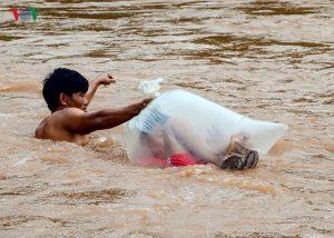 Hàng chục học sinh chui vào túi nylon qua suối đến trường